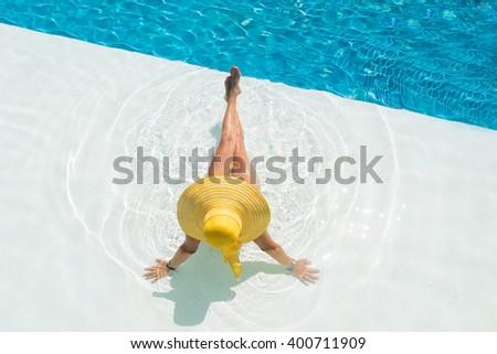 Young woman in bikini wearing a yellow straw hat by the swimming pool - stock photo