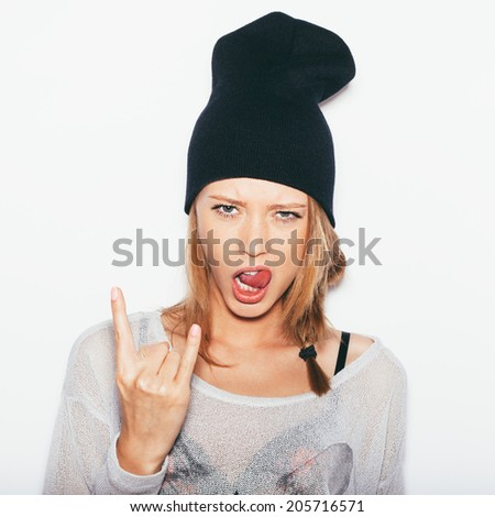 Young woman in black beanie giving the Rock and Roll sign.  Toned. White background, not isolated - stock photo