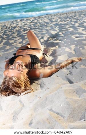 young woman in black bikini on beach - stock photo