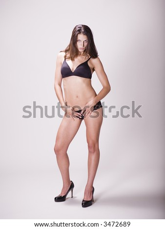 Young woman in black bra and panties with her hands on her hips