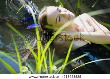 Young woman in black corset lying in the water and touches face