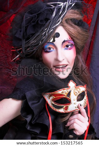 Young woman in black dress and with artistic make-up posing with mask
