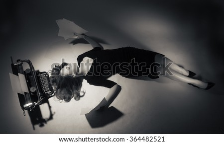 Young woman in black dress lies near a typewriter. - stock photo