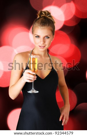 Young woman in black elegant dress holding goblet with champagne - stock photo
