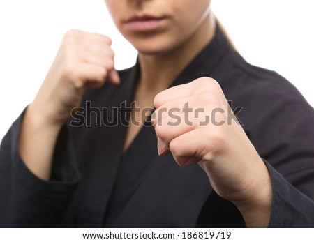 Young woman in black kimono is ready to fight, isolated over white - stock photo