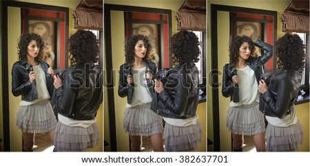 Young woman in black leather jacket and gray short tutu skirt looking into a large mirror. Beautiful curly dark hair girl posing in front of a wall mirror, indoors shot. Fashionable brunette model. - stock photo