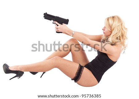 Young woman in black lingerie holding pistol, sitting position - stock photo