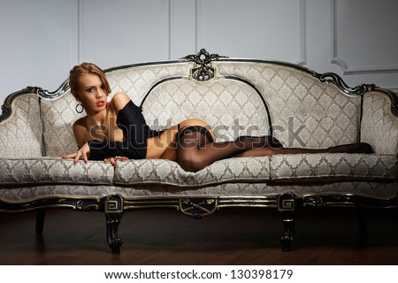 Young woman in black lingerie lying on the couch - stock photo