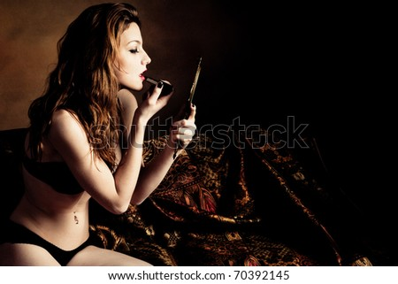 young woman in black lingerie sit on bed and apply lipstick, holding hand mirror, studio shot - stock photo