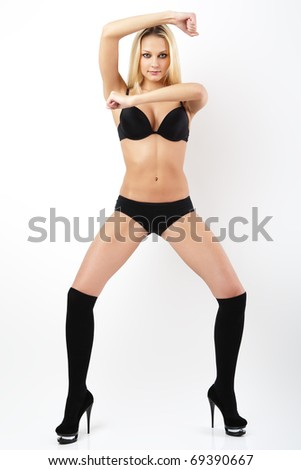 Young woman in black panties, bra and shoes. - stock photo