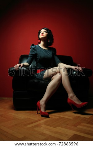 Young woman in black skirt and white dress sitting on black sofa - stock photo
