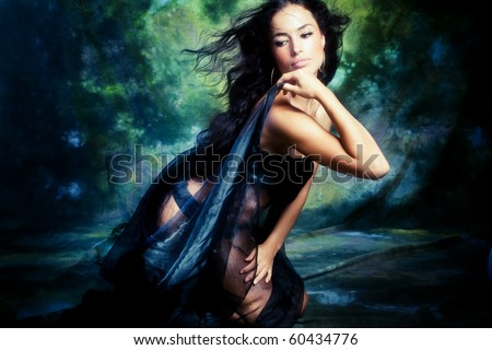 Young woman in black studio shot fantasy background - stock photo