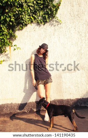young woman in black top tank, shiny shorts and  hat with dog stand in front wall summer day - stock photo