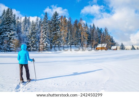 Young woman in blue down jacket walking towards remote mountain hut during cold winter - stock photo