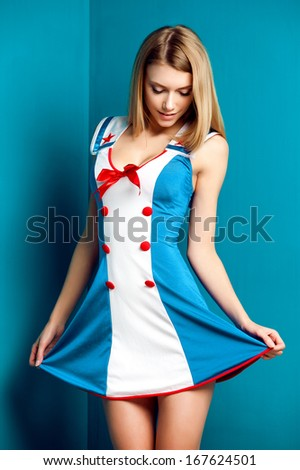 young woman in blue dress posing in studio - stock photo