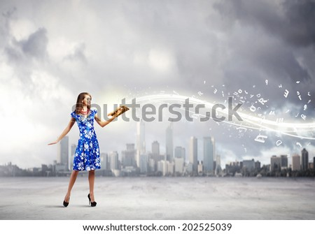 Young woman in blue dress reading book