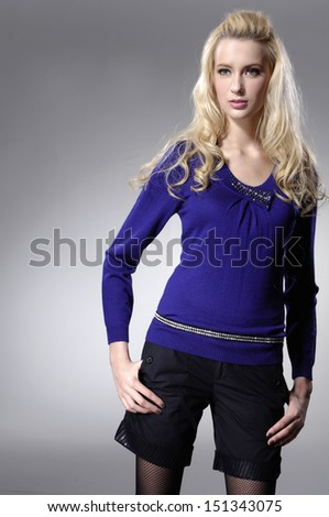 young woman in blue dress standing posing on light background - stock photo