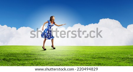 Young woman in blue dress walking on green globe
