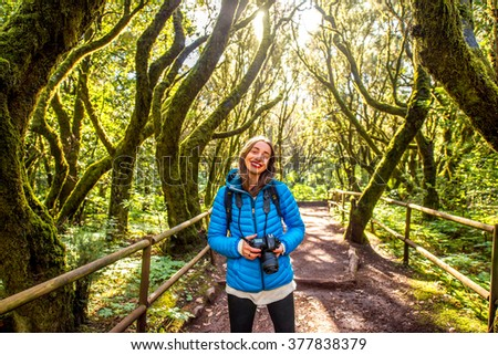 Young woman in blue jacket traveling with backpack and photo camera in beautiful evergreen forest in Garajonay park on La Gomera island on Canary island, in Spain - stock photo