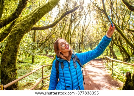 Young woman in blue jacket traveling with backpack, photographing with smart phone beautiful evergreen forest in Garajonay park on La Gomera island on Canary island, in Spain - stock photo