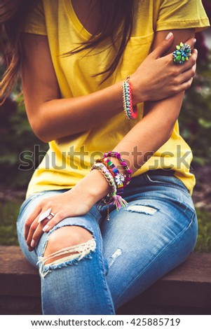 young woman in blue jeans and yellow t-shirt focus on hand with colorful bracelets - stock photo