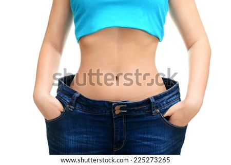 young woman in blue jeans showing how much weight she lost ,isolated, white background. - stock photo