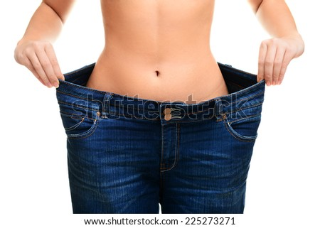 young woman in blue jeans showing how much weight she lost ,isolated, white background.