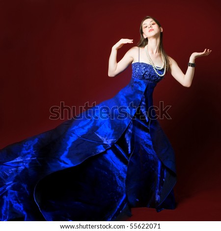 Young woman in blue long dress on red backgrounds - stock photo