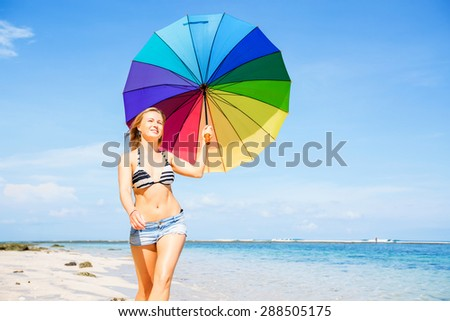 Young woman in blue shorts with colourful rainbow umbrella walking on beach with wite sand and clear blue sky on background