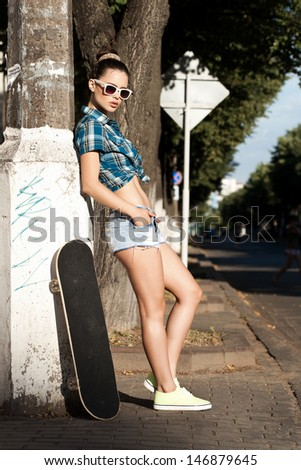Young woman in blue sunglasses standing with a skateboard in the daytime. Outdoors, lifestyle - stock photo