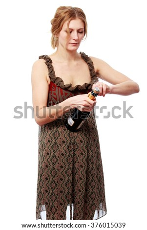 Young woman in bright dress opening a bottle of champagne, isolated on white background