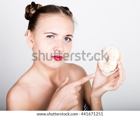 young woman in bright makeup eating a tasty donut with icing. Funny joyful woman with sweets, dessert. dieting concept. junk food. girl licking their fingers - stock photo
