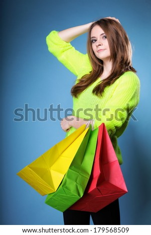 young woman in bright vivid colour sweater with paper multi coloured shopping bags on blue background. Sales and discounts concept.