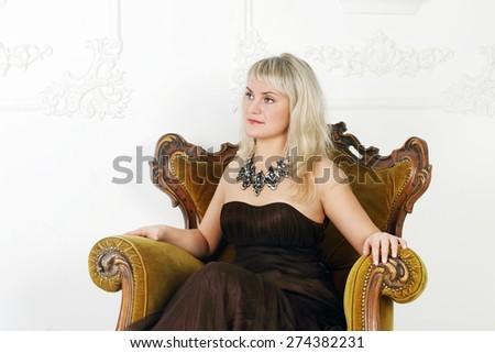 Young woman in brown dress sits in vintage chair and looks away in white studio  - stock photo