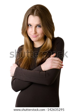 young woman in brown  sweater embracing herself isolated on white background - stock photo