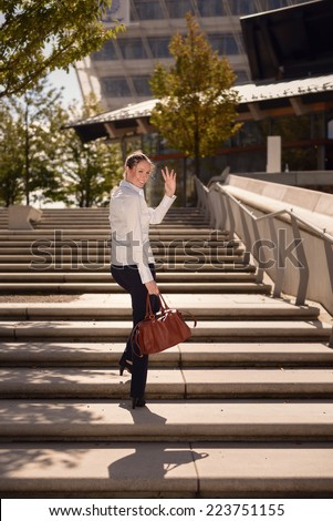 Young Woman in Business Attire with Elegant Bag Walking on Concrete Stairs Going Up While Take a Pose for a While and Wave One Hand, Emphasizing Goodbye. - stock photo