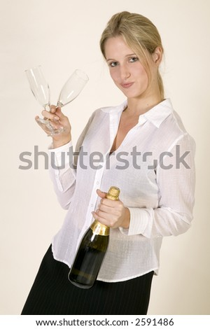 Young woman in business clothes with a bottle of champagne and two glasses against a white background