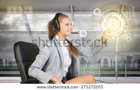 Young woman in business office sitting and pressing on holographic screen with icon on abstract digital background