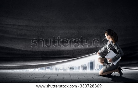Young woman in business suit opening cement curtain - stock photo