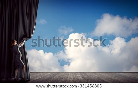 Young woman in business suit opening color curtain of stage - stock photo