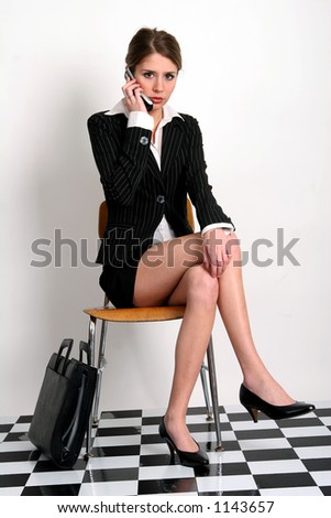 Young woman in business suit talking on her cell phone with her briefcase next to her. - stock photo