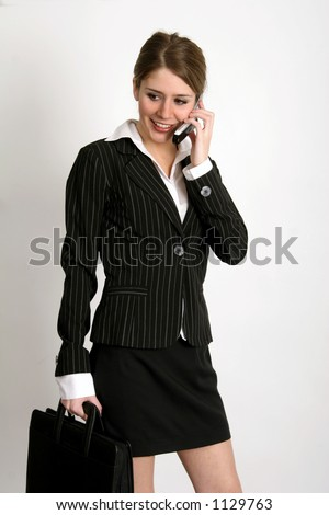 Young woman in business suit talking on the phone while holding a briefcase - stock photo