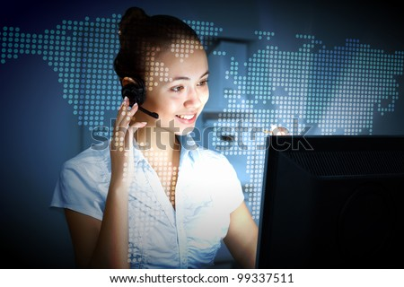 Young woman in business wear in headset working with computer - stock photo