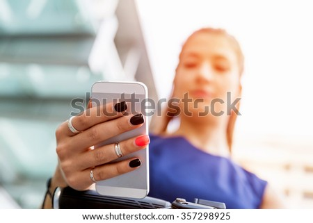 Young woman in business wear on bicycle and holding mobile phone - stock photo