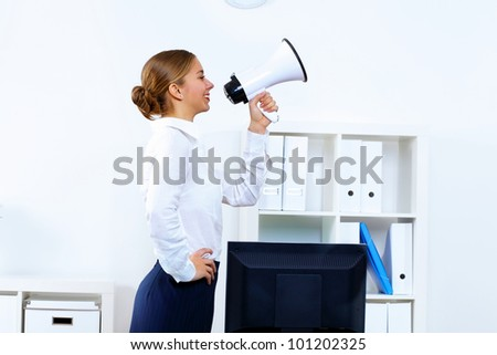 Young woman in business wear with megaphone in office