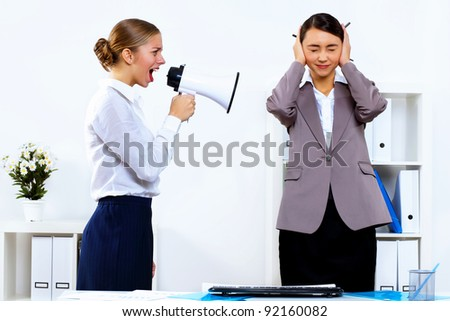 Young woman in business wear with megaphone in office - stock photo