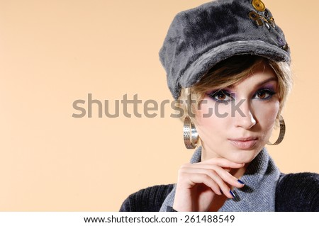 young woman in cap posing on light background
