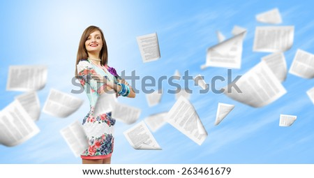 Young woman in casual and paper flying in air - stock photo