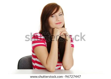 Young woman in casual clothes sitting at the desk, isolated on white - stock photo