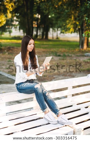 Young woman in casual clothes using tablet or phone on the sunbed or bench in the park  - stock photo